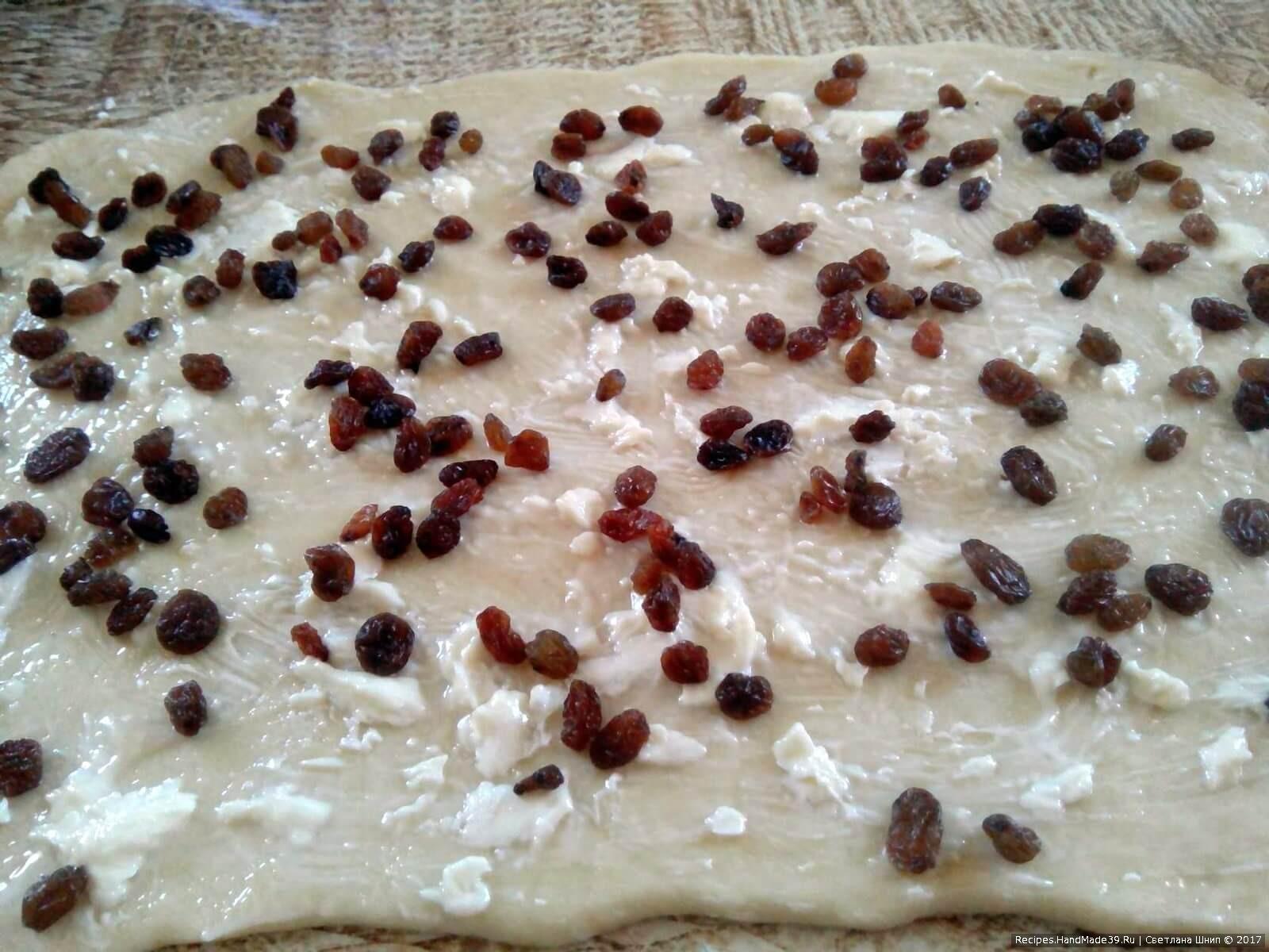Посыпать пласт теста мускатным орехом, изюмом и миндальными лепестками