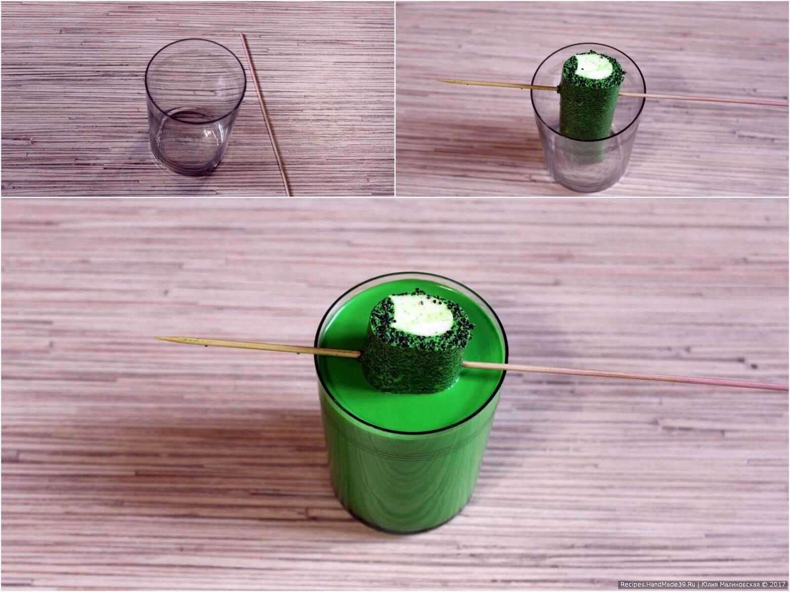 Приготовить 250-граммовый стакан и шпажку. Из плёнки извлечь серединку, вставить в центр стакана, зафиксировать её шпажкой. Залить остальным зелёным желе.