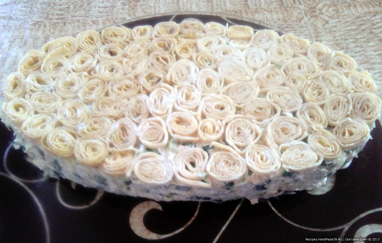 Выложить готовый салат в подготовленную форму, где на дне уже выложены блинные рулончики. Накрыть блюдо крышкой, перевернуть и снять форму (салатник)