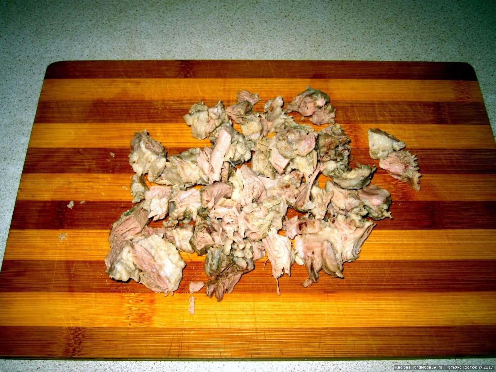 Отвариваем бульон на свиной грудинке, затем мясо достаём и нарезаем его небольшими кусками