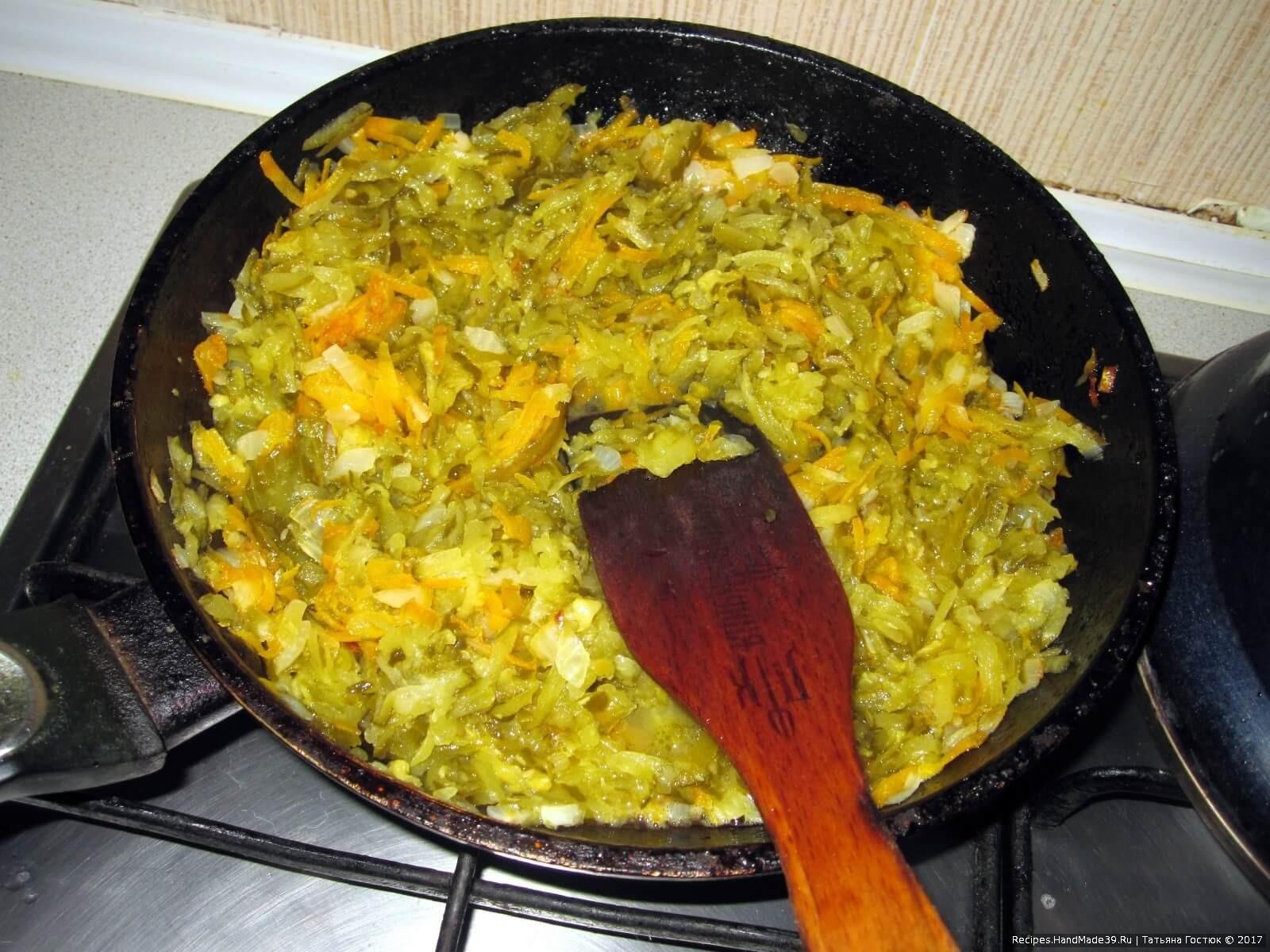 Добавляем к луку и морковке натёртые на крупной тёрке кислые огурцы, тушим под крышкой минут 15