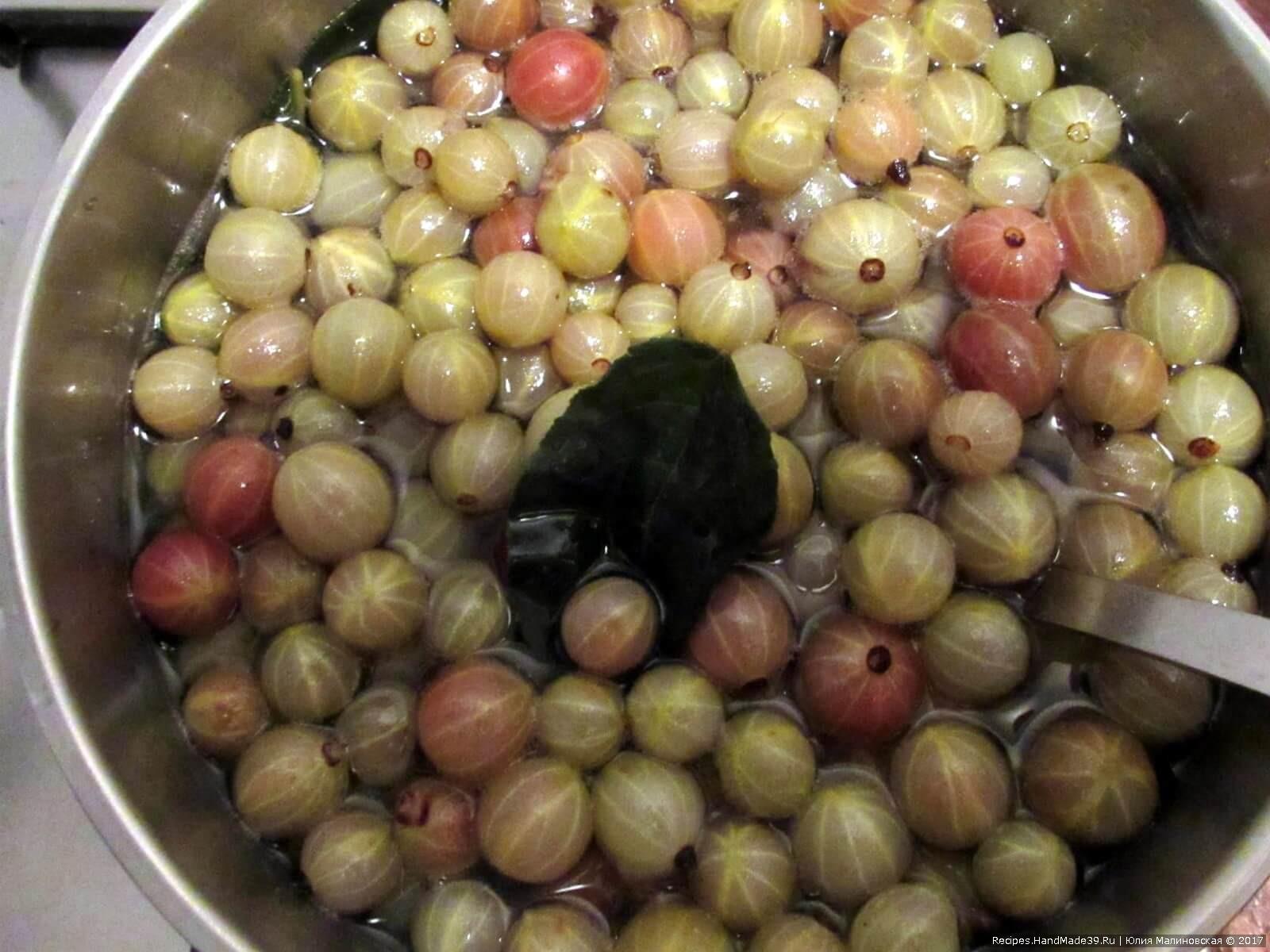 Всыпать в сироп ягоды крыжовника, варить на очень медленном огне 10 минут