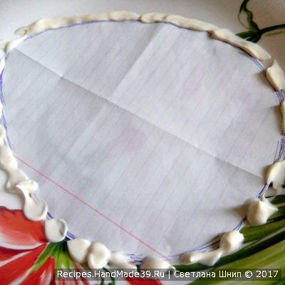 Прикладываем вырезанный лист на тарелку и делаем контур из майонеза