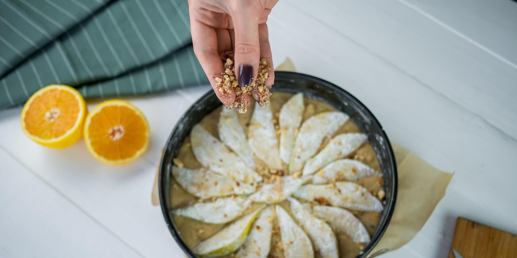 Сверху разложите грушу и посыпьте орехами
