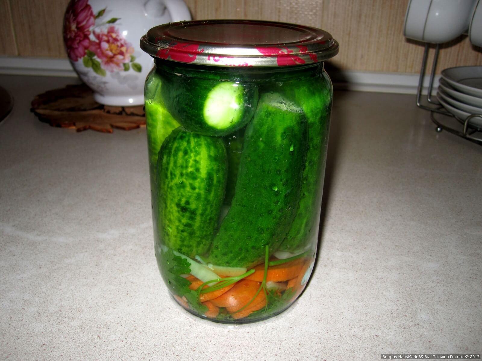 На дно банок укладываем немного зелени, моркови и лука, сверху – огурцы