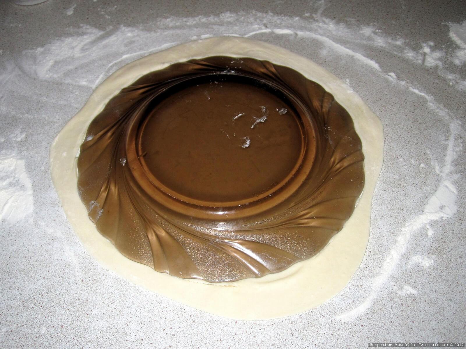 Прикладываем к тесту тарелку или крышку (у меня диаметром около 18 см) и острым ножом по её контуру вырезаем круг