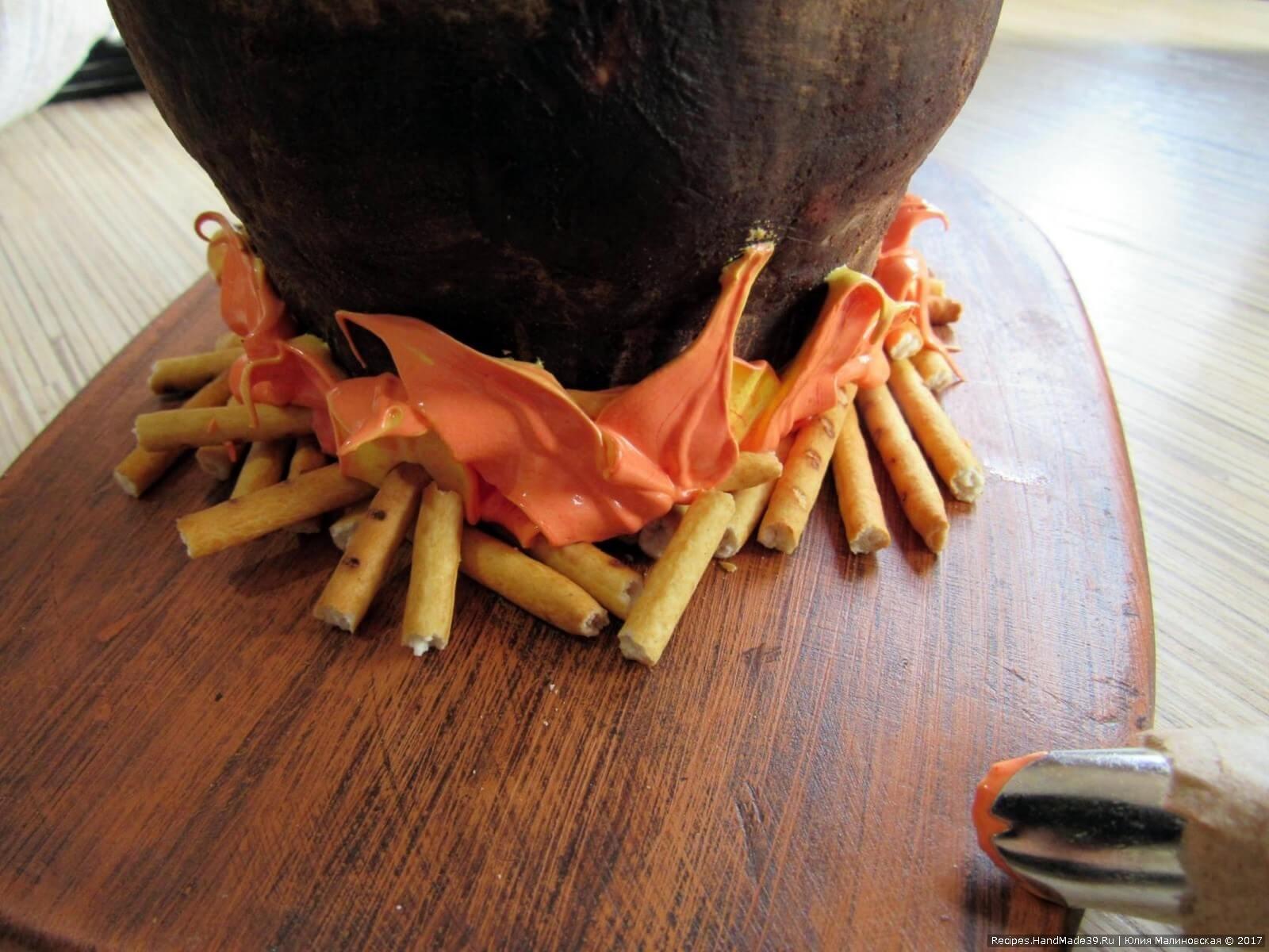 Выдавить крем через насадку «листик» внизу чугунка, имитируя языки огня