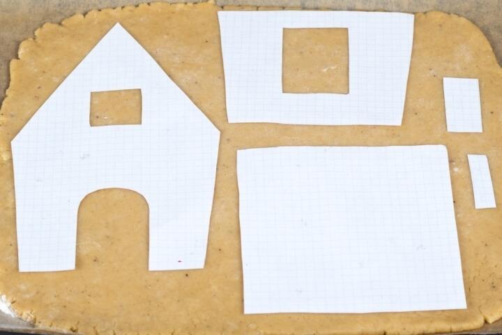 Вымесить тесто ещё раз и раскатать на листах пергамента для выпечки до толщины 0,5 см. Разложить трафарет (чертеж) деталей на тесто