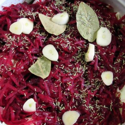 В ёмкость выложить слой капусты, слой свёклы, специи – розмарин, перец молотый, лавровый лист, чеснок. Всё повторить