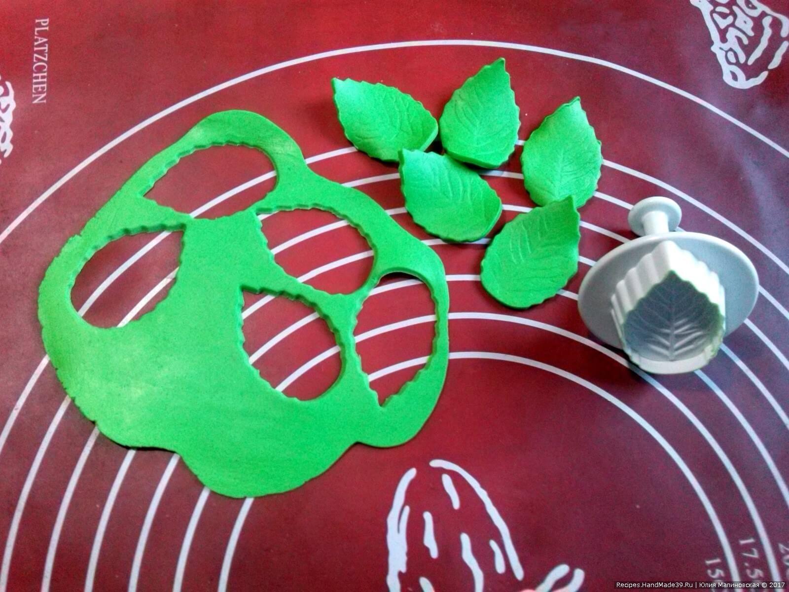 Из мягкого зелёного шоколада вырезать плунжером листики. Дать шоколаду застыть