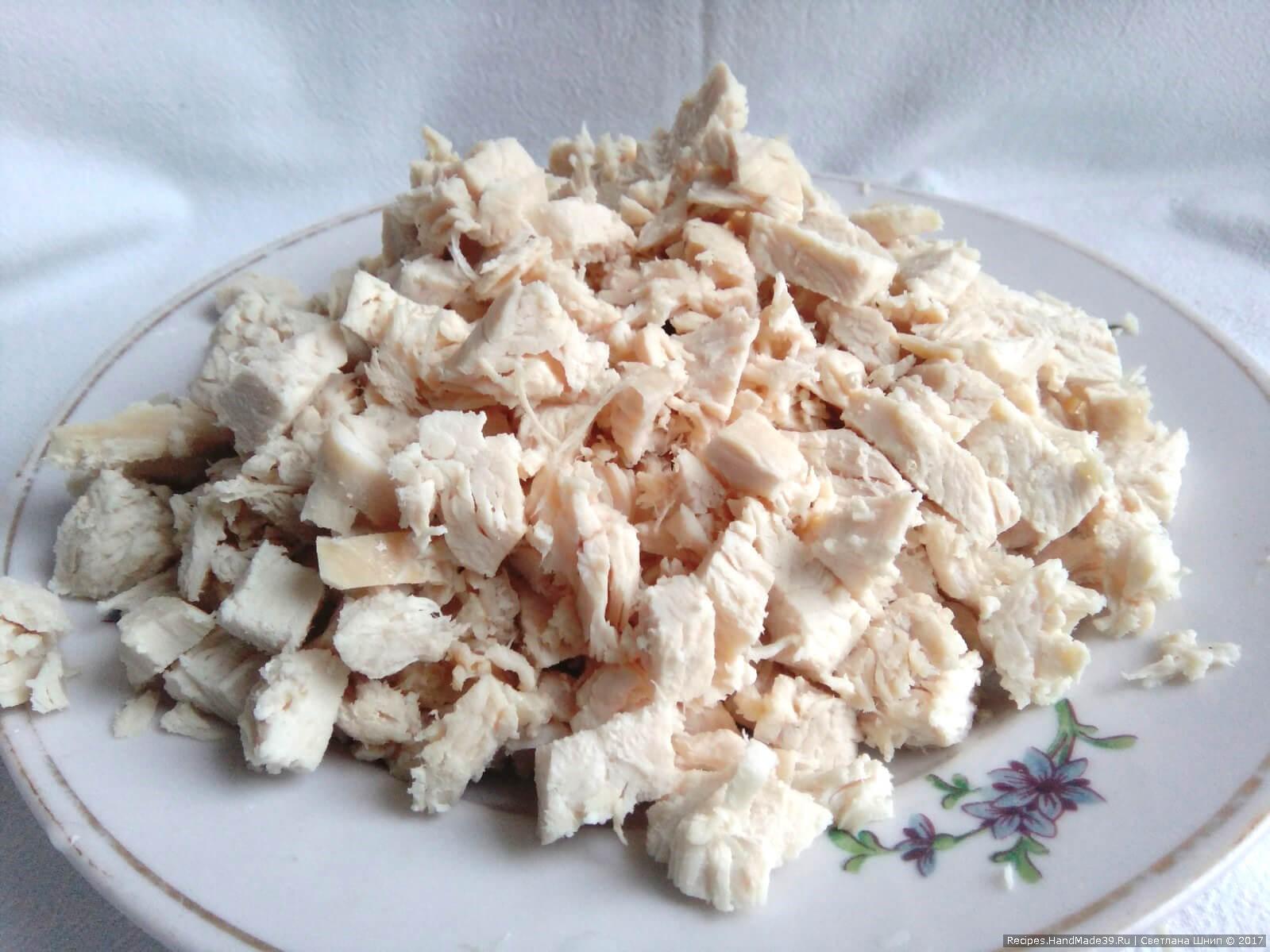 Куриные грудки отварить в подсоленной воде, добавить в воду лавровый лист. Готовое мясо выложить, мелко порезать и переложить в свободную тарелку