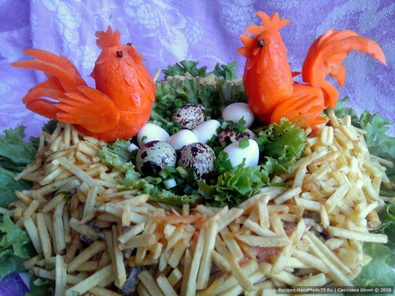 В образовавшийся круг выложить листья салата поменьше, в «гнездо» уложить варёные перепелиные яйца. Из моркови вырезать петушков, посадить их в гнездо
