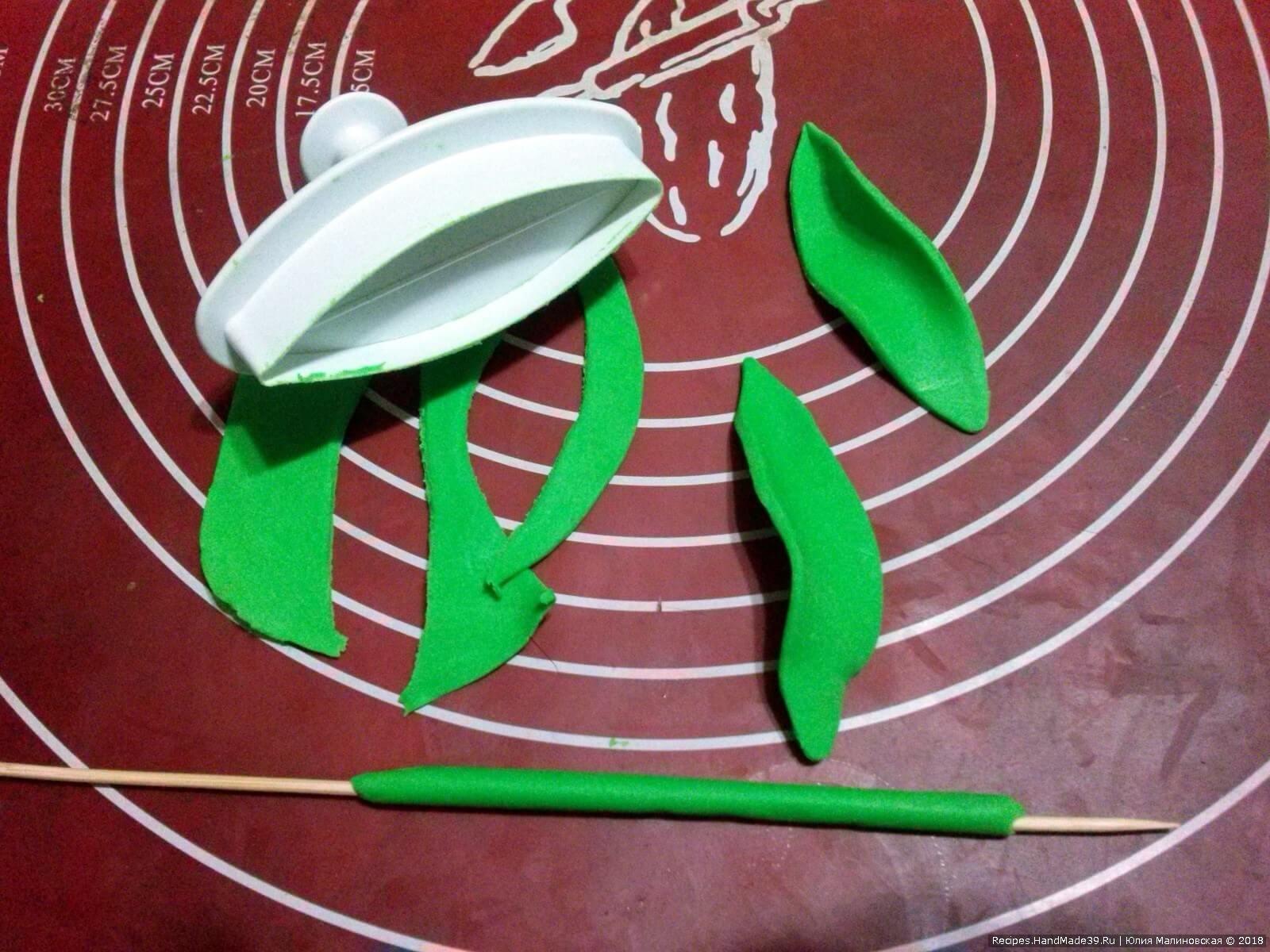Выемкой «лилия» вырезать листья из зелёного пластичного шоколада