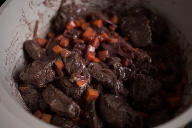 Говядина по-бургундски – фото шаг 3. Вернуть мясо обратно в сковороду. Туда же отправить кубики моркови вместе с чесноком, солью и перцем. Перемешать