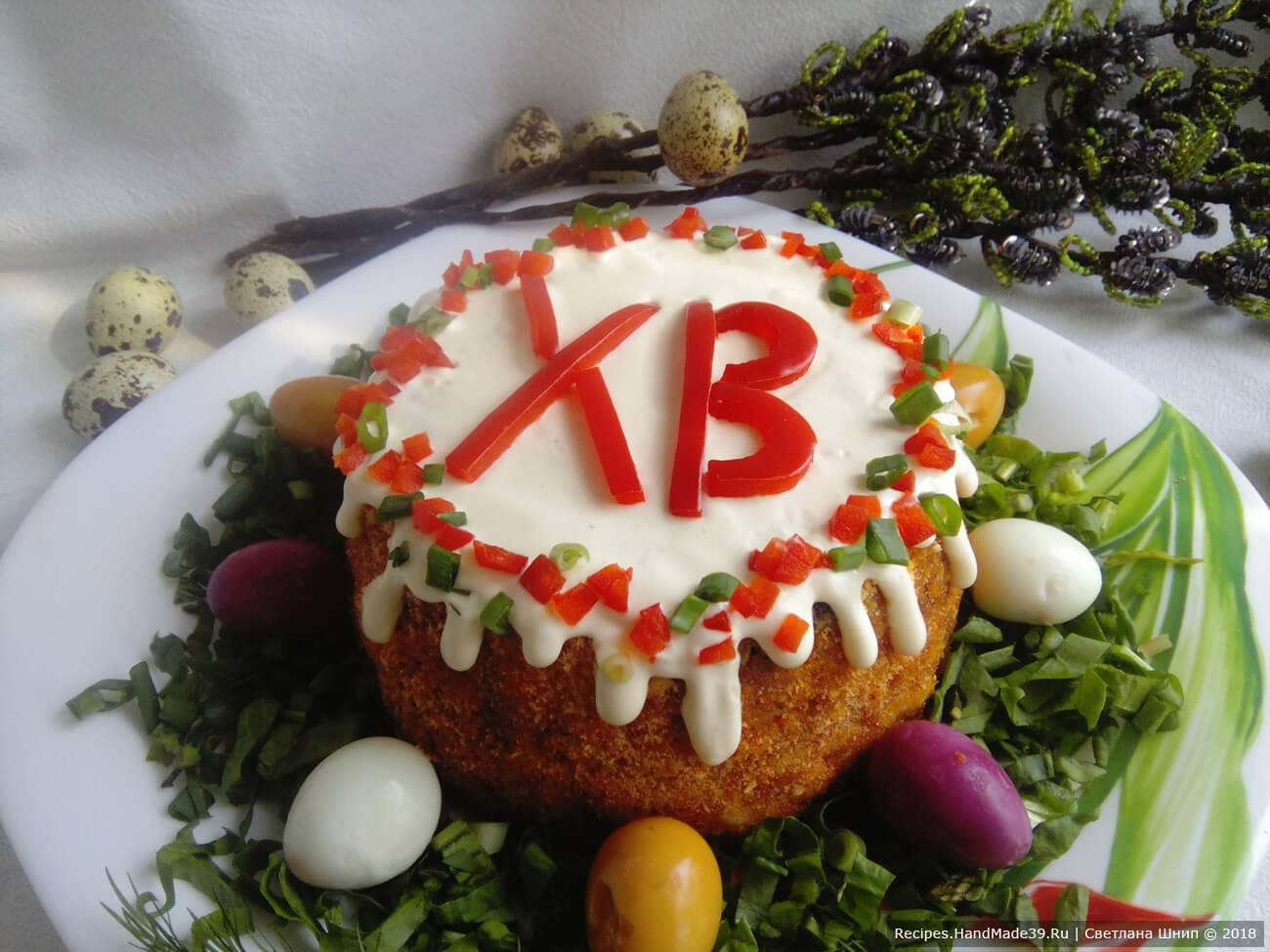 Выложить окрашенные яйца вокруг салата. Сверху выложить буквы ХВ, вырезанные из помидора или красного сладкого перца. По окружности сделать декоративную кайму из кубиков помидора и зелёного лука