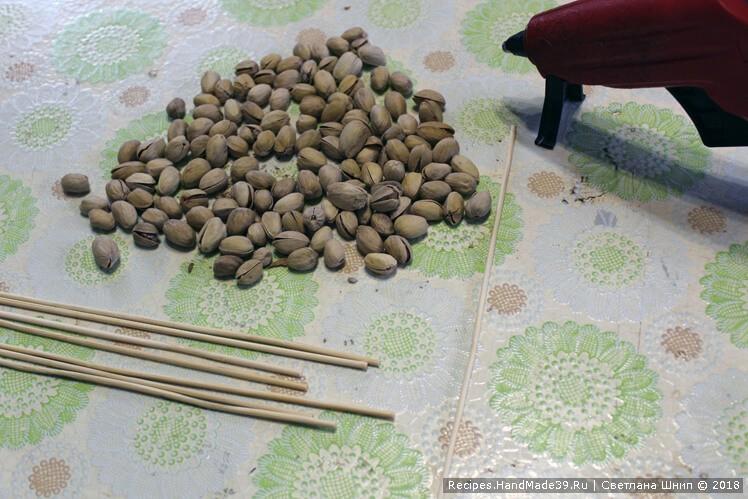 Фисташки в кожуре с помощью клеевого пистолета приклеить к деревянным шпажкам