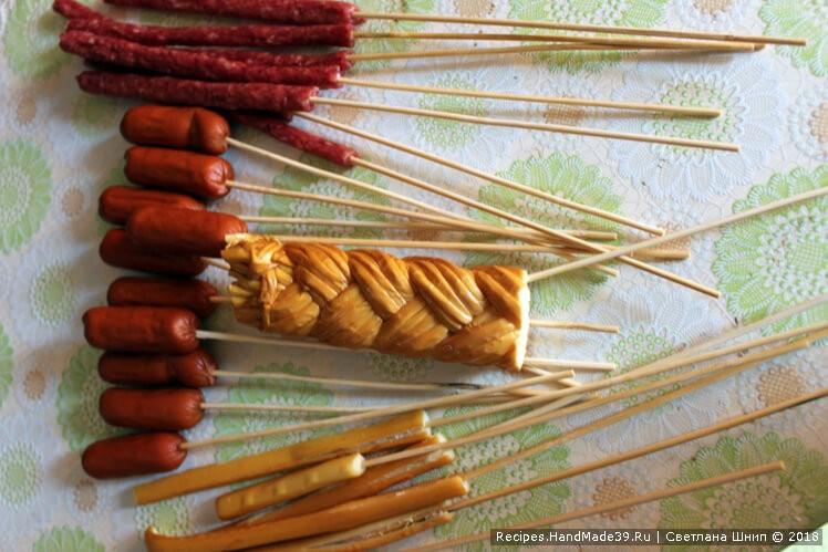 Копчёные колбаски и сыр осторожно насадить на деревянные шпажки