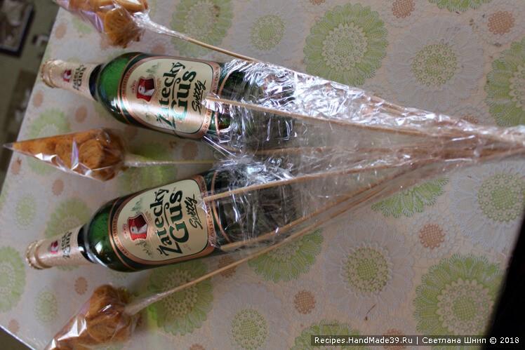 Закрепить скотчем кулёчки с сухариками и веточки с фисташками и арахисом на заготовке с бутылками