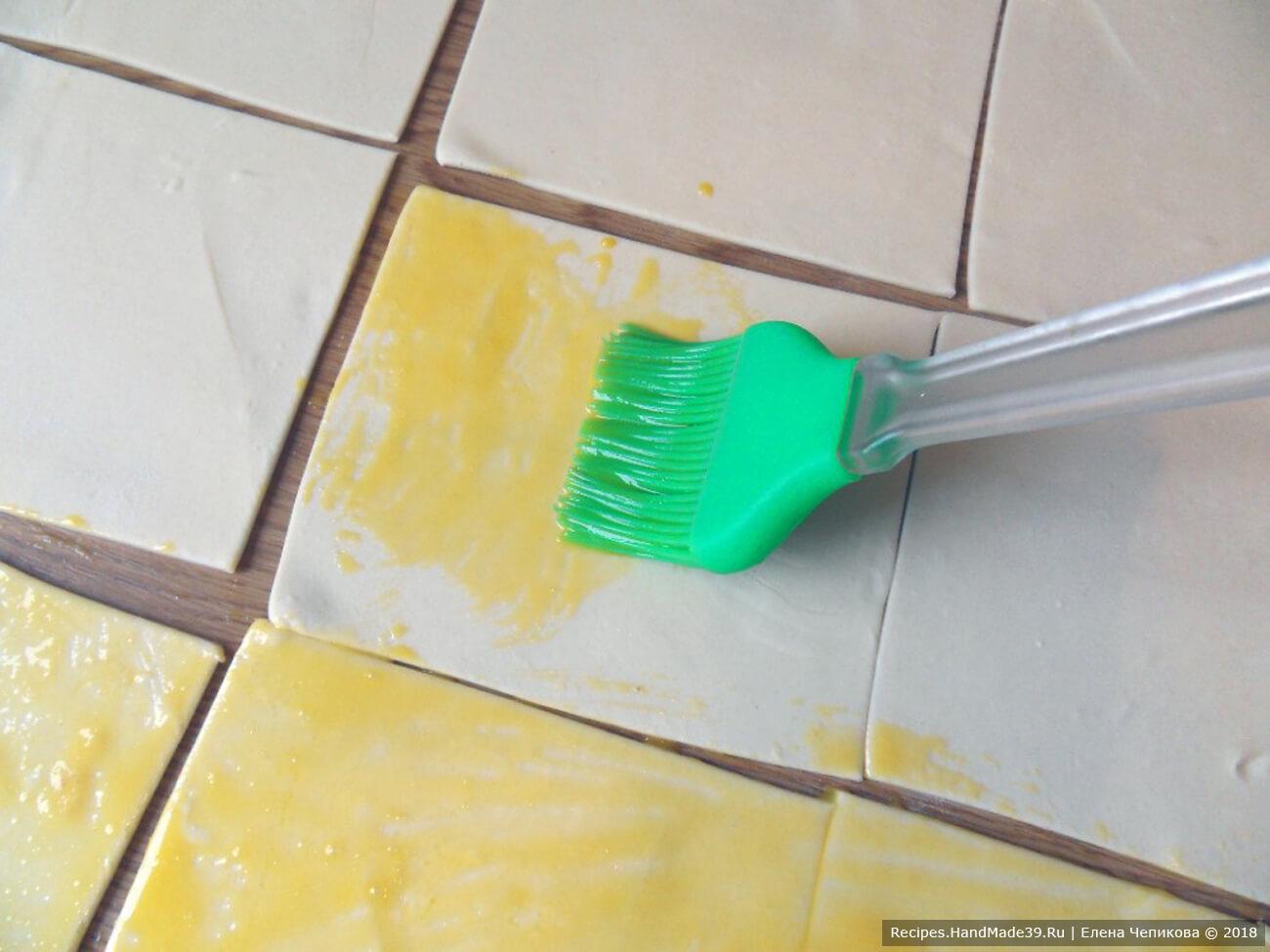 Слоёное тесто раскатать, разрезать на квадраты, смазать яичным желтком