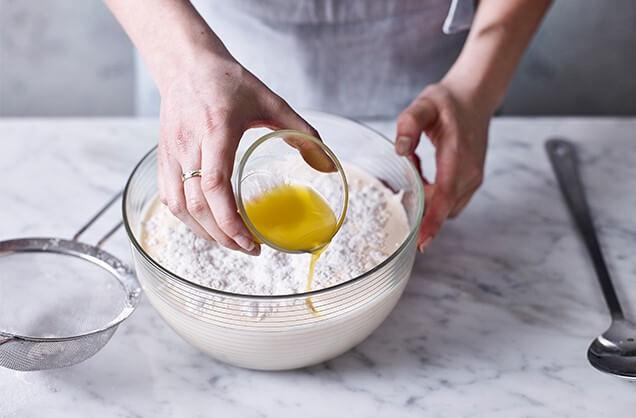 Просеять 130 г муки и 0,75 ч. л. разрыхлителя для теста. Сверху полить растопленным сливочным маслом (35 г).