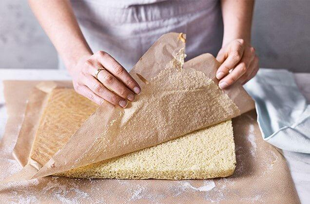 Осторожно перевернуть горячий бисквит на это пергамент, снять пергамент, на котором бисквит выпекался.