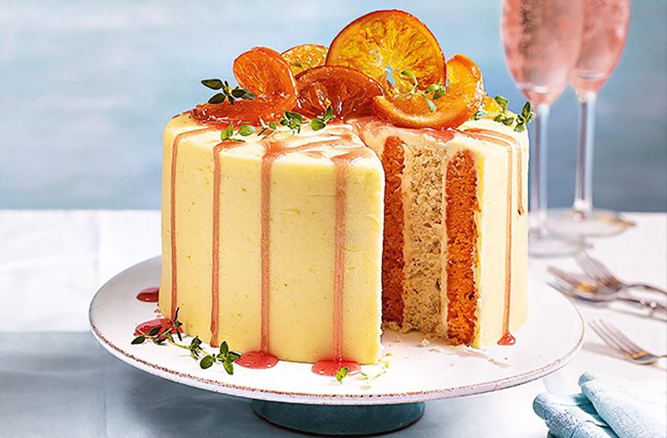 Выложьте апельсины сверху торта, разбросайте веточки тимьяна. Полейте сиропом так, чтобы он стекал по бокам.