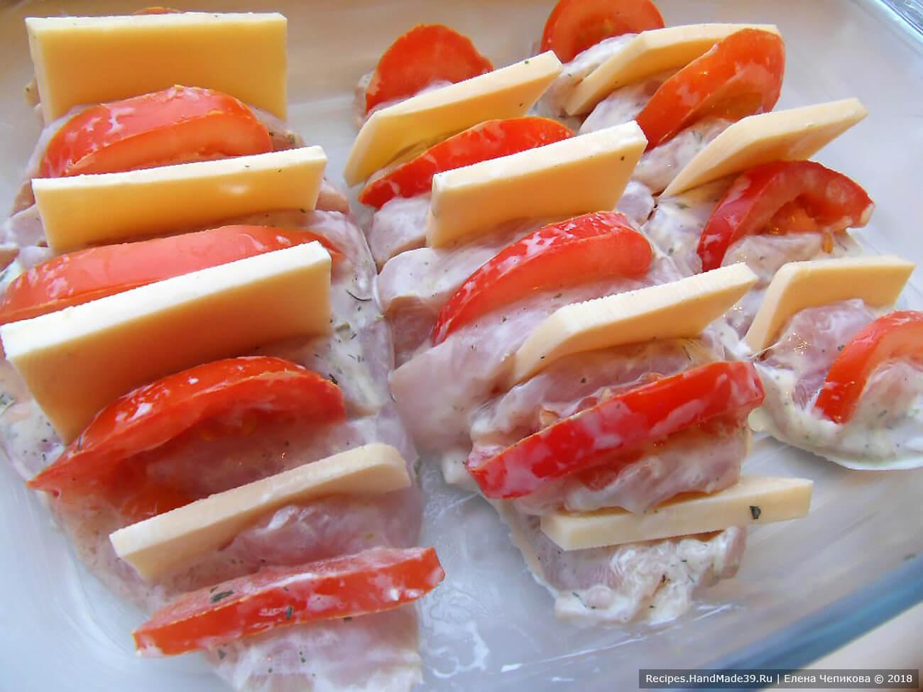 В надрезы поочерёдно вложить кусочки помидора и сыра