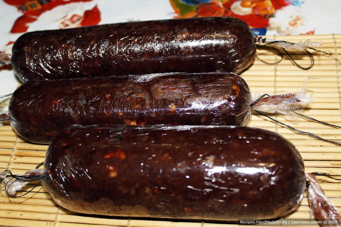 Расстелить пищевую плёнку, выложить часть шоколадной массы. Плотно завернуть плёнку, формируя колбаску