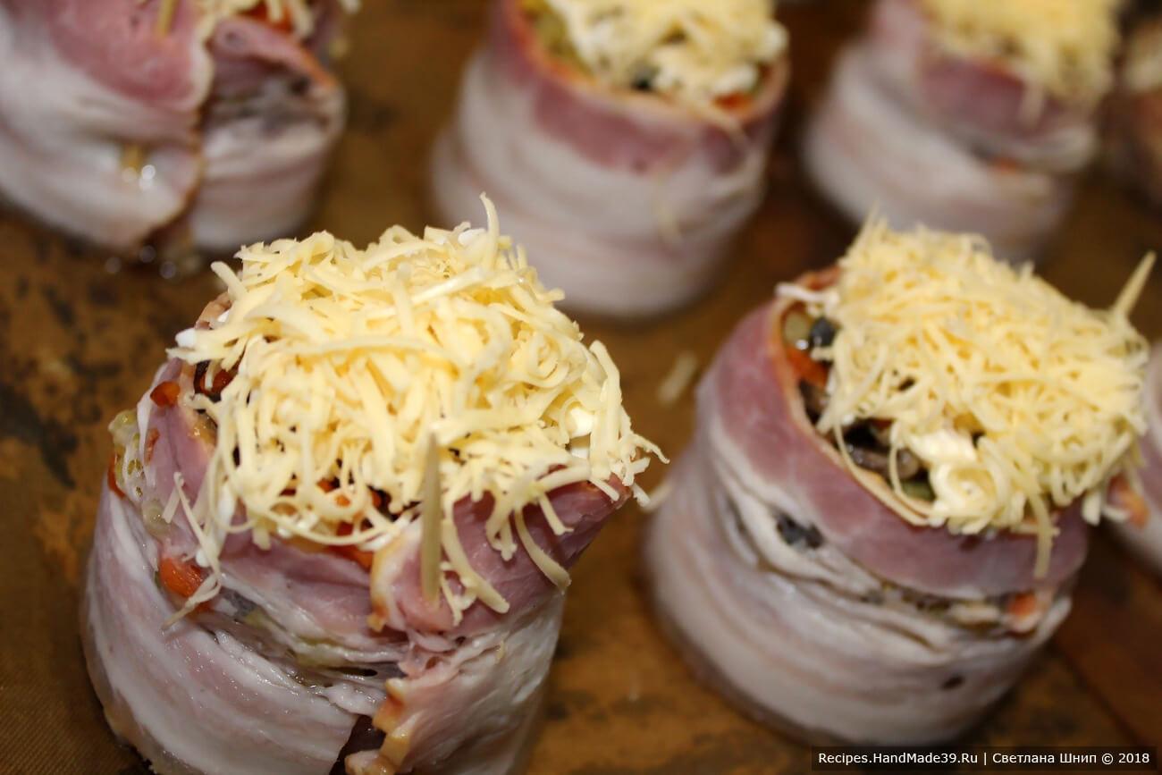 Сыр натереть на тёрку, посыпать им каждое «гнездо» сверху