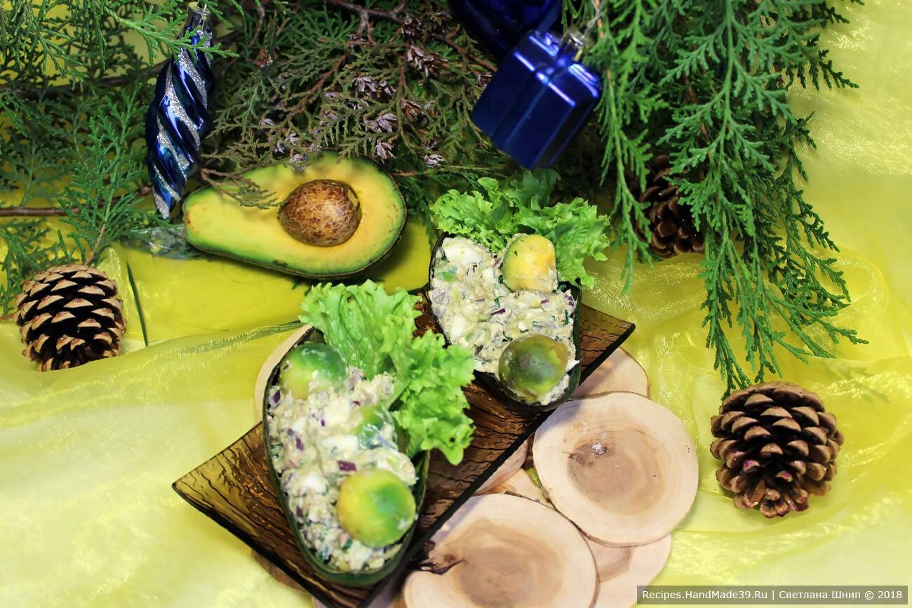 Выложить салат в «лодочки» от авокадо. Украсить шариками авокадо и зеленью. Приятного аппетита!