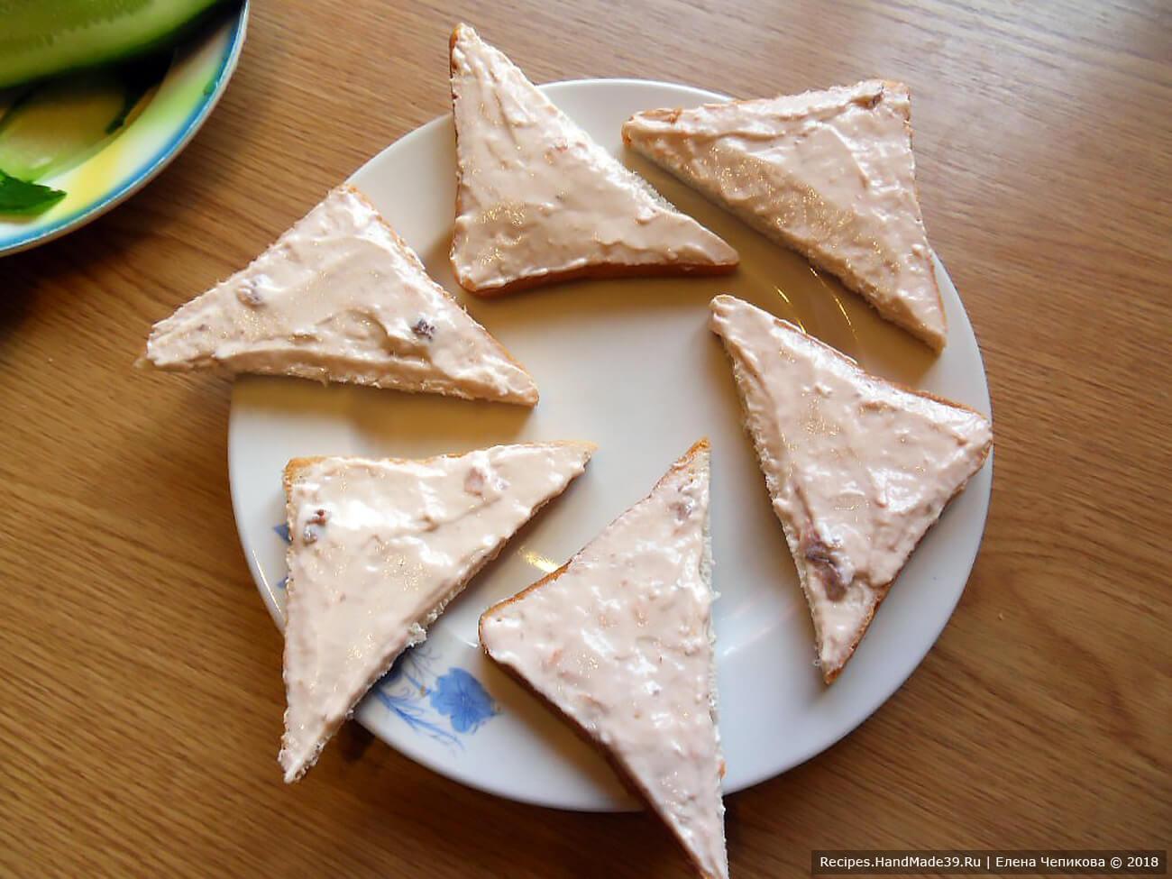 Тостовый хлеб разрезать по диагонали (на треугольники). Намазать на хлеб сырно-рыбную пасту