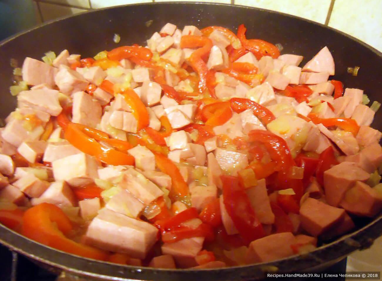 В глубокой сковороде разогреть подсолнечное масло, обжарить лук в течение 2 – 3 минут. Добавить полоски перца и колбасу. Тушить 5 минут. Посолить, поперчить