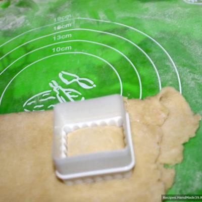 Разрезать тесто фигурным ножом или выемкой для теста так, чтобы начинка была в середине каждого печенья