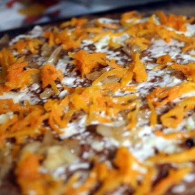 Сверху распределить лук, морковь и чеснок, пропущенный через пресс