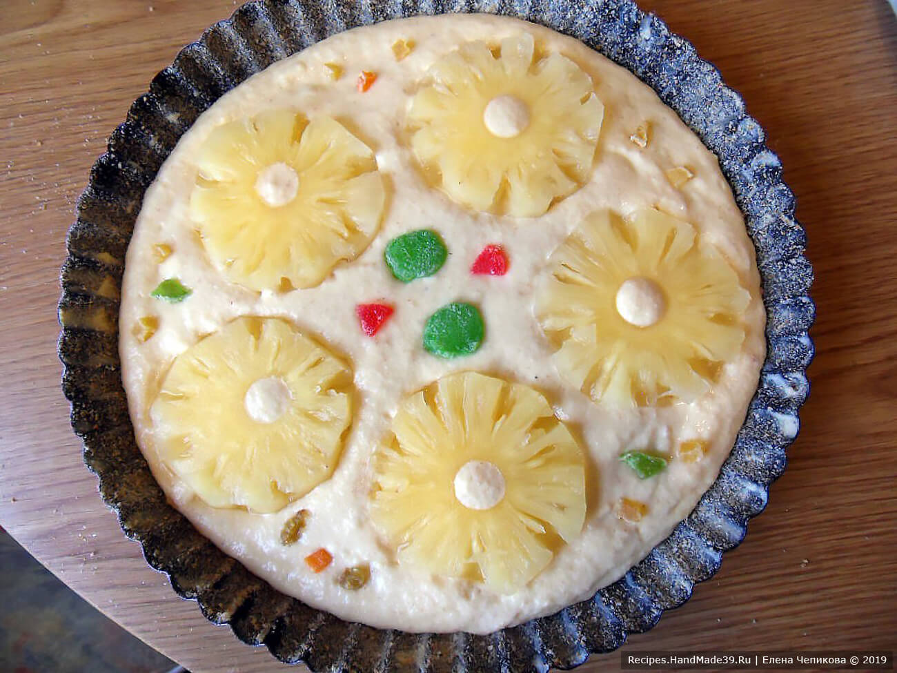 Выложить на тесто кольца ананасов, слегка вдавить в тесто. Дополнительно можно выложить кусочки цукатов, мармелад