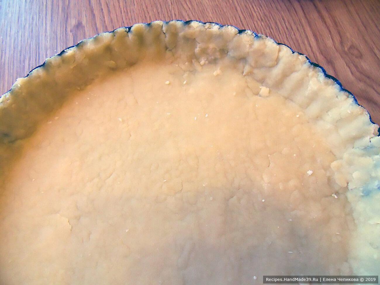 Песочное тесто раскатать в пласт. Уложить в форму, сделать бортики