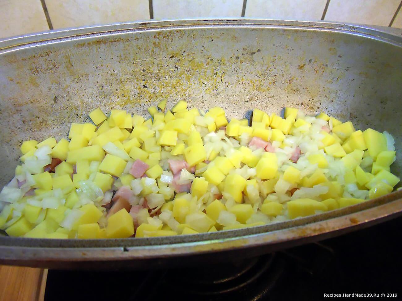 Как только начнёт выделяться жир, добавить нарубленный лук и картофель, нарезанный мелкими кубиками