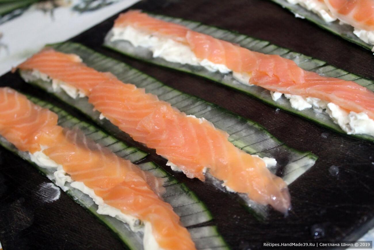 Выложить пластины лосося поверх творожного сыра