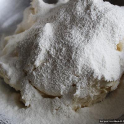 Стол присыпать мукой, выложить тесто и понемногу добавлять муку, вымешивая тесто