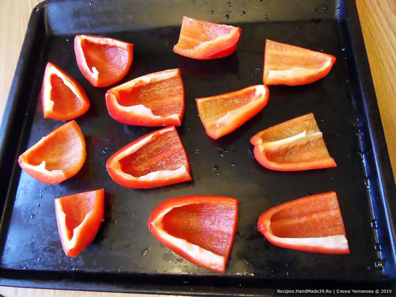 Сладкий перец разрезать на четвертинки, удалить семена и сердцевину. Перец выложить на сухой противень и запекать 15 минут при температуре 250 °C