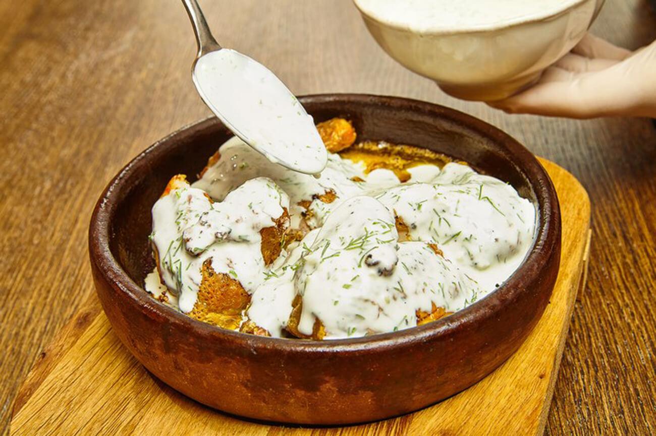 Полить сметанно-чесночным соусом. Для соуса смешать сметану с мелко порезанным укропом, измельченным чесноком и солью