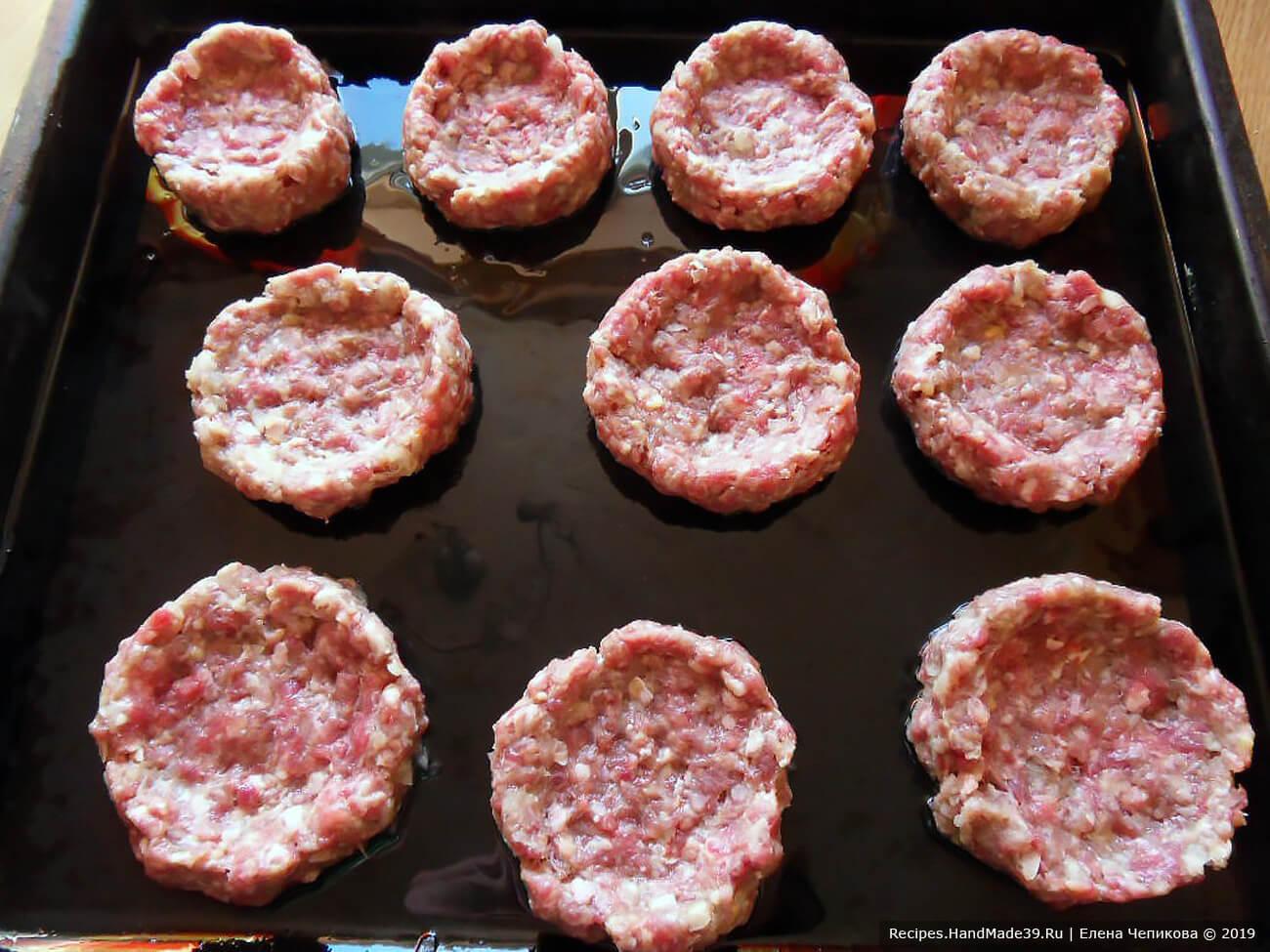 Из полученного мясного фарша сформировать круглые котлетки, в каждой сделать углубление. «Гнёзда» выложить на противень, смазанный растительным маслом