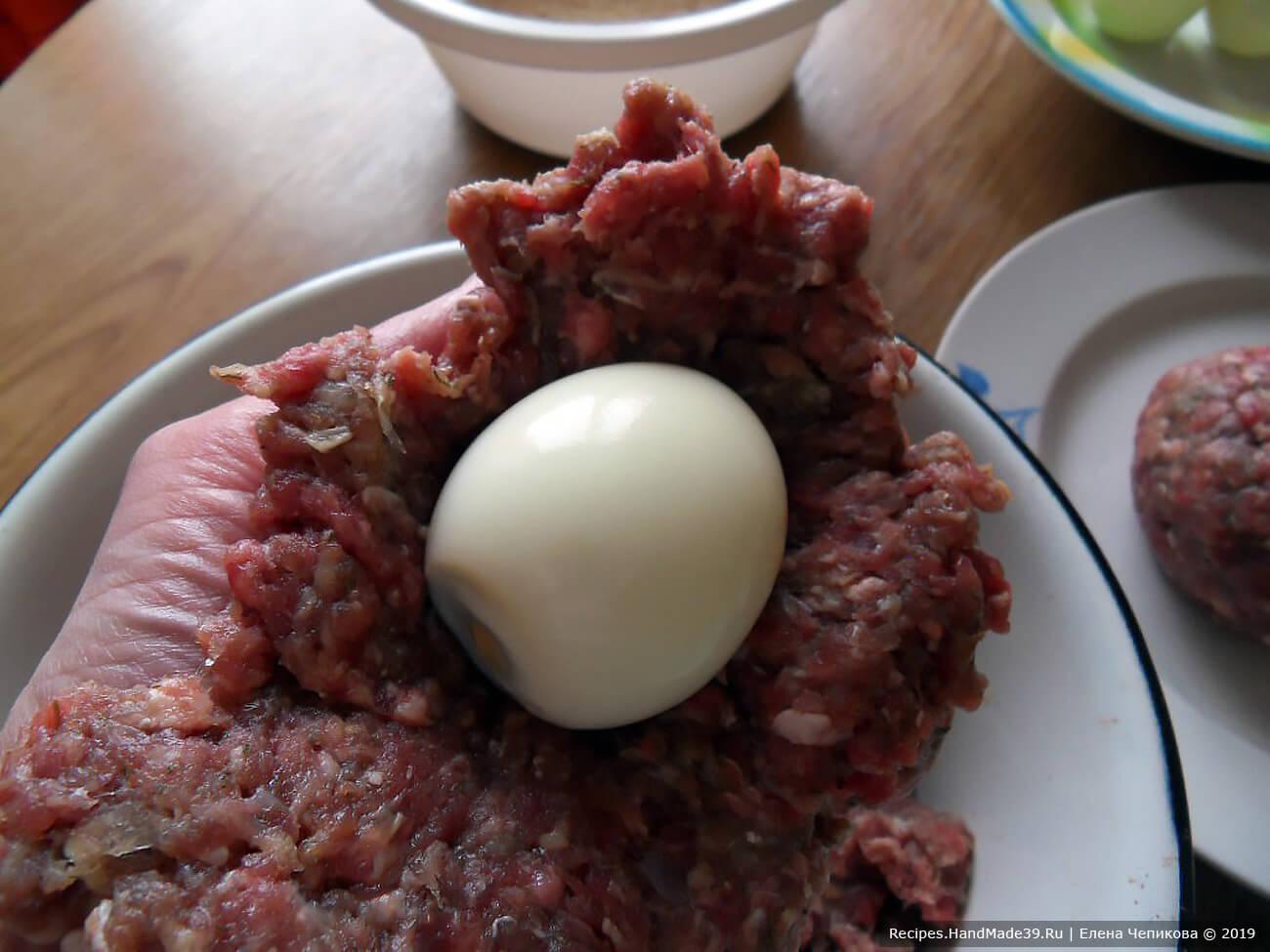 Фарш посолить, добавить специи (по желанию), хорошо вымешать. Разделить на равные части по количеству яиц. Из каждой части фарша сделать лепёшку, в центр которой выложить яйцо