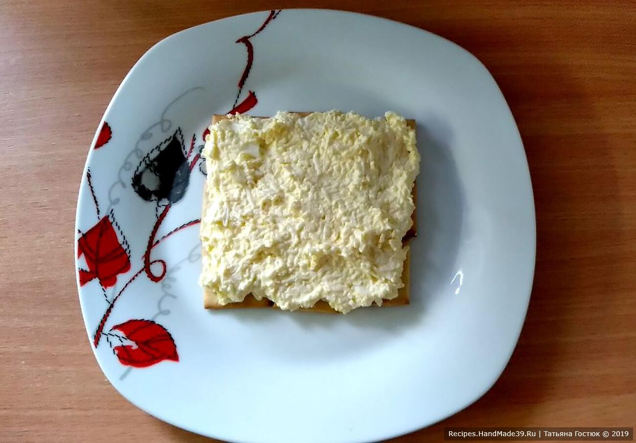 На слой крекера выкладываем смешанное с майонезом яйцо