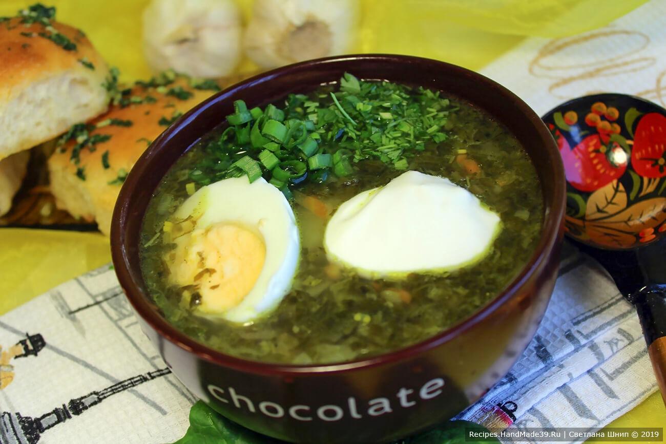 Подавать зелёные щи с нарезанными отварными яйцами и сметаной