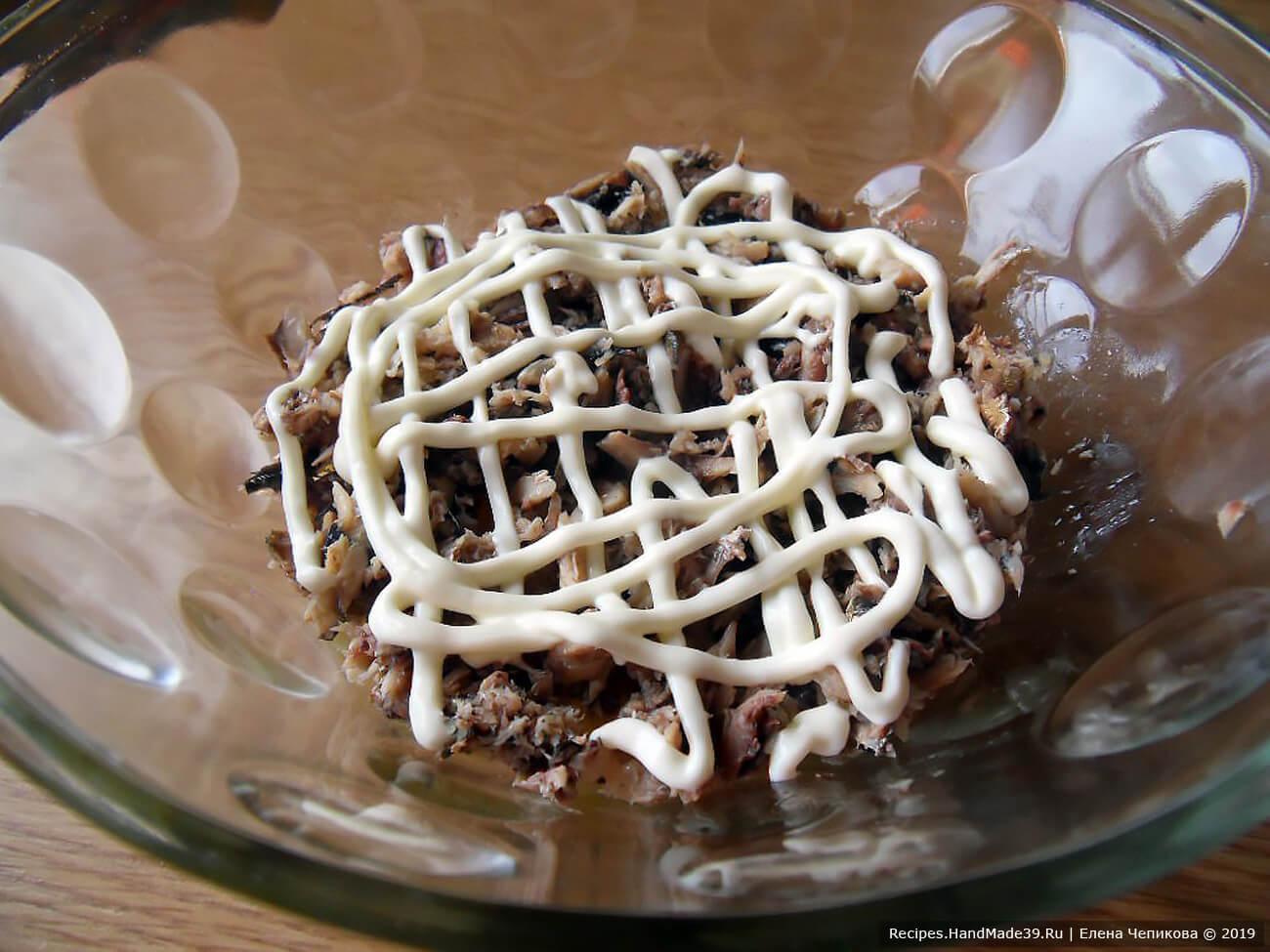 2-й слой салата – размятые шпроты + сетка из майонеза