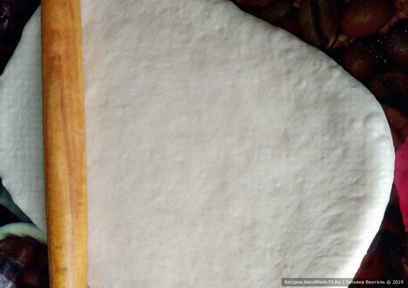 Подошедшее тесто обмять и раскатать в пласт толщиной 0,6 см