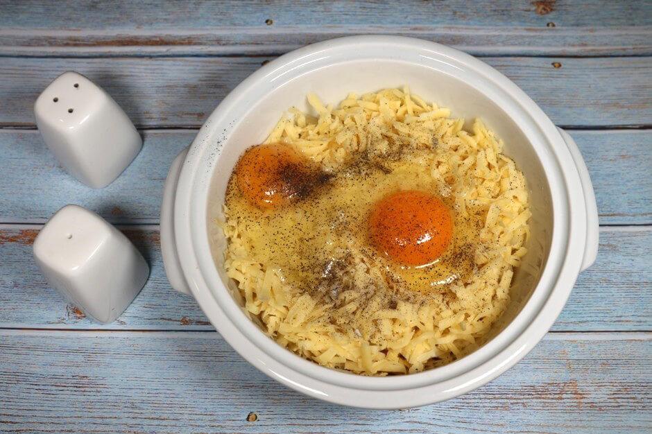 К картофелю добавить натёртый сыр на средней тёрке. В эту же ёмкость вбить 2 яйца, приправить солью и чёрным молотым перцем. Перемешать все ингредиенты