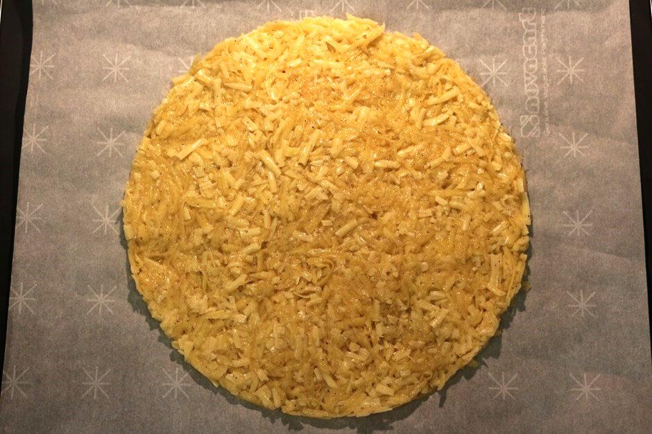 Далее следует на противень выложить пекарскую бумагу и на неё выложить в форме круга получившуюся картофельно-сырную смесь. Выпекать картофель следует в течение 12 минут