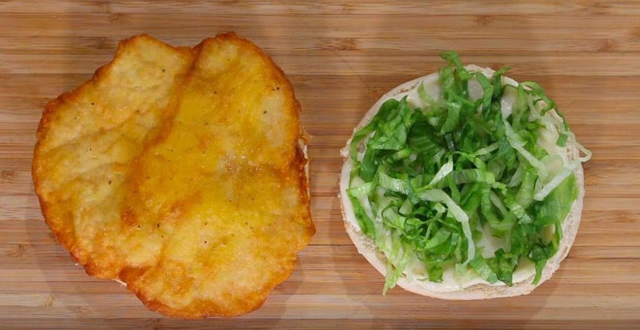 Булочку для гамбургера разогреть в микроволновке в течение 30 секунд. На нижнюю часть булочки положить куриную котлету. На верхнюю часть булочки – специальный соус и сверху нарезанный лист салата Айсберг